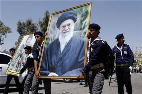 Iraqi Hezbollah march in Baghdad with a portrait of Iran's Supreme Leader