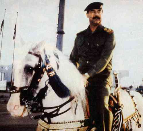 Saddam Hussein riding his white Arabian horse through his Victory Arch in 1990.
