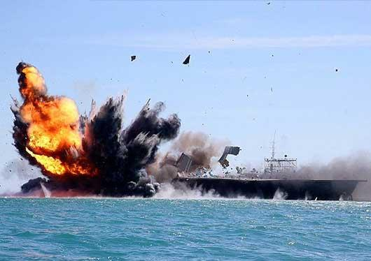 The Iranian IRGC navy destroys its mock U.S. Nimitz-class aircraft carrier during its most recent military exercises in February 2015.
