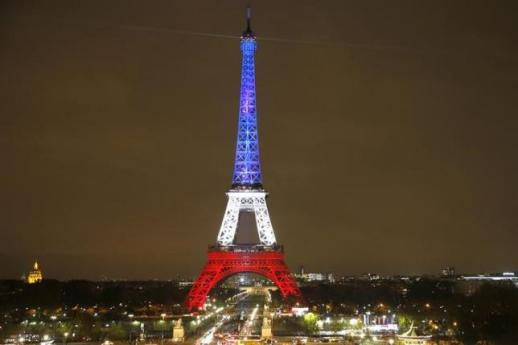 The Eiffel Tower is lit with the blue, white and red colors of the French flag following the attack on Paris. (REUTERS/Charles Platiau)