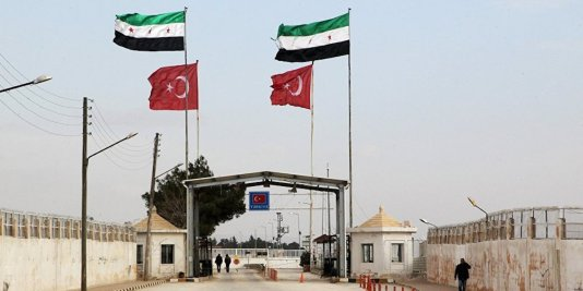 A Turkish-Syrian checkpoint seen from the Syrian side.  Note the colors of the four horsemen.